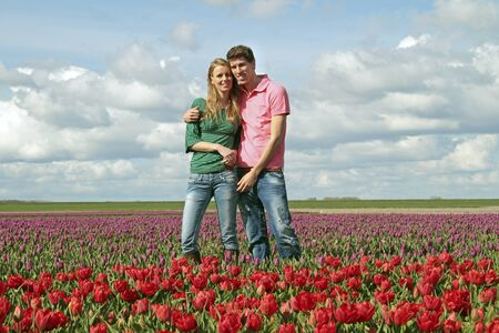 Young happy couple in the tulip fields from the Netherlands photo