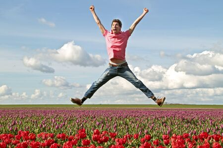 Young enthousiastic guy jumping up from the tulip fields in the Netherlands