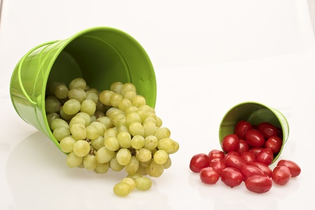 Tomatoes and grapes in a green bucket