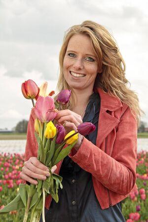 Schöne Frau mit Tulpen in den Tulpenfelder in den Niederlanden