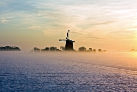 Traditional windmill at twilight with fog and snow in winter in the Netherlands Stock Photo - 13728305