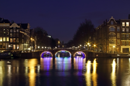 City scenic from Amsterdam by night at the river Amstel in the Nethrlands Standard-Bild