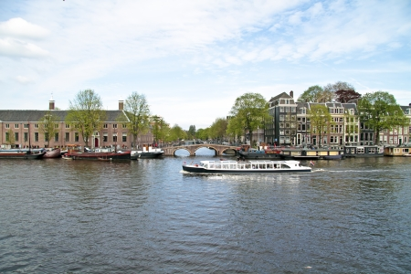 amstel: Cruising on the river Amstel in Amsterdam the Netherlands Stock Photo