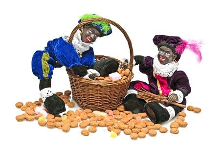 Twee zwarte piet met een mand vol pepernoten en snoep bij de Kerstman feest op 5 december in Nederland Stockfoto