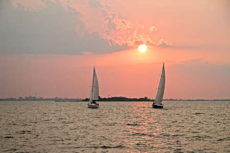 watersport: Sailing on the IJsselmeer at Pampus in the Netherlands with sunset Stock Photo