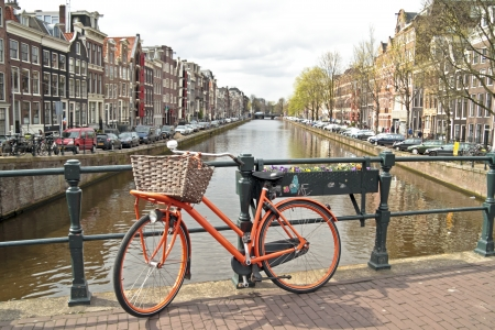 holland: Orange bike on the bridge in Amsterdam city in the Netherlands Stock Photo