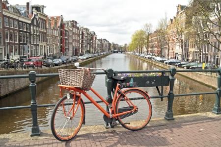 Oranje fiets op de brug in Amsterdam stad van Nederland Stockfoto