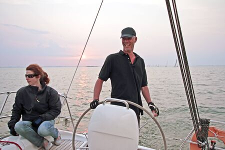 ijsselmeer: Happy sailor sailing at sunset on the IJsselmeer in the Netherlands