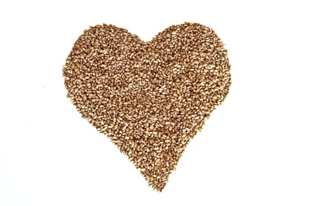 Heart of wheat grains on a white background photo