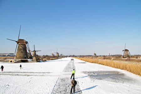 typically dutch: Ice skating at Kinderdijk in the Netherlands Stock Photo