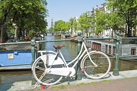 westerkerk: White bicycle in Amsterdam city center with the Westerkerk in the background in the Netherlands
