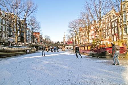 Schaatsen op de grachten in Amsterdam, Nederland in de winter Redactioneel