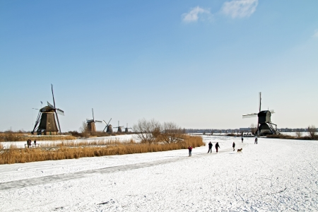 typically dutch: Ice skating at Kinderdijk in the Netherland