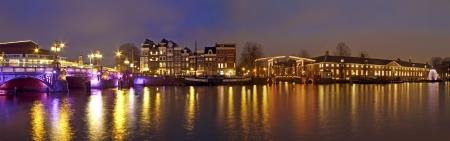 Panorama van Amsterdam binnenstad met de Amstel in Nederland 's nachts