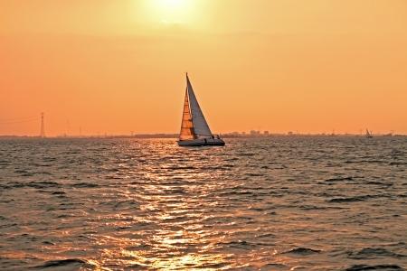 ijsselmeer: Sailing at sunset on the IJsselmeer in the Netherlands Stock Photo