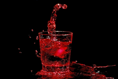 Ice cube splashing into a glass of red wine photo