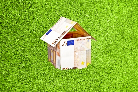 Little house from euro money in green grass Stock Photo - 17715227