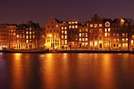 amstel: Medieval houses along the Amstel at night in Amsterdam the Netherlands