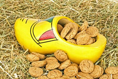 klompen: Traditional dutch wooden clog with  gingernuts in straw for 5 december santa claus feast in the Netherlands Stock Photo
