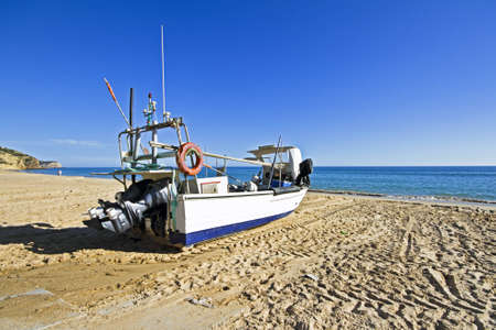 Fishing boat at the beach at Salema in Portugal photo