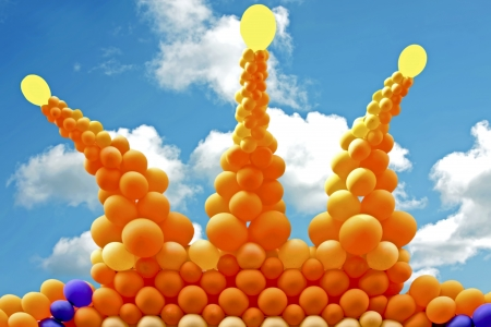 Crown from orange balloons against a blue sky