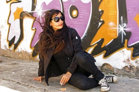 Smoking woman in black at the graffiti brick wall photo