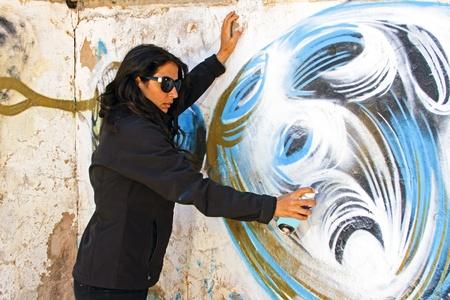depressive: Woman in black spraying at a graffiti brick wall