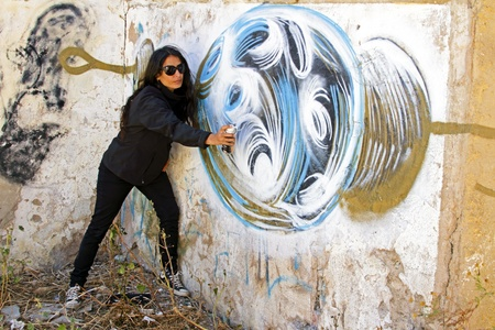 Woman in black spraying at a graffiti brick wall photo