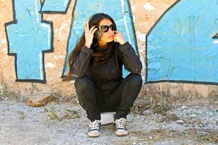 Smoking woman phoning at a graffiti wall photo