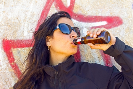 Woman drinking beer in front of a graffiti wall photo