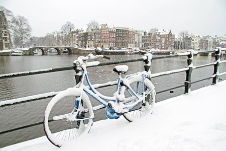 Bicycle in Amsterdam the Netherlands covered in snow Stock Photo - 20793691