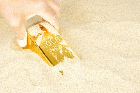 goldbar: Digging up a goldbar in sand Stock Photo