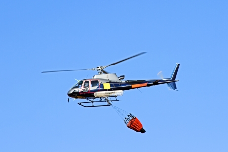 Fire fighter helicopter with a waterbag photo