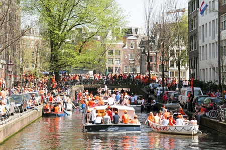 AMSTERDAM - APRIL 30: Amsterdam canals full of boats and people in orange during the celebration of queensday on April 30, 2012 in Amsterdam, The Netherlands Stock Photo - 21067435