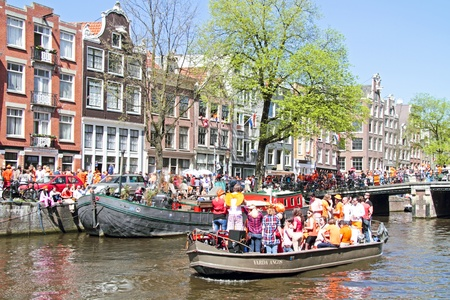 cruiseboat: AMSTERDAM - APRIL 30: Amsterdam canals full of boats and people in orange during the celebration of queensday on April 30, 2012 in Amsterdam, The Netherlands Editorial