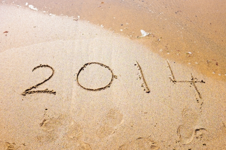 Happy New Year, 2014 written in sand at the beach photo