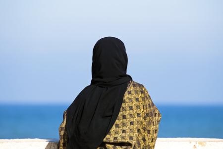 iraq: Arab woman with Islamic headscarf looking over the ocean Stock Photo