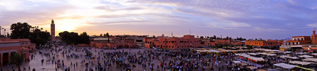 Sunset at Djemaa el Fna market in Marrakesh, Morocco, with Koutubia Mosque at the back
