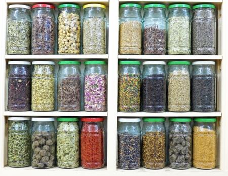 herbolaria: surtido de frascos de vidrio en los estantes en la tienda de herbolario en Marrakech, Marruecos, que contienen hierbas y especias con fines medicinales y culinarias