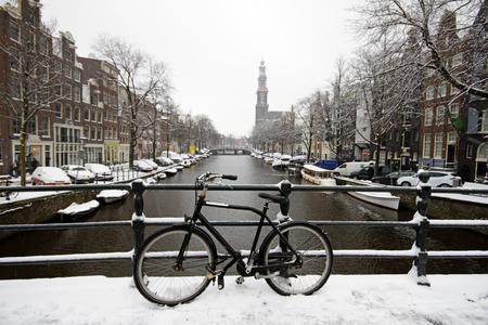 Amsterdam bedekt met sneeuw, met de Westerkerk in de winter in Nederland Stockfoto