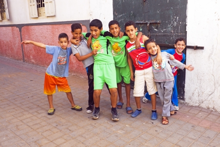distributing: RABAT, MOROCCO - October 15 2013 : Kids in the streets on Eid al-Adha. The festival is celebrated by sacrificing a sheep or other animal and distributing the meat to relatives, friends, and the poor.