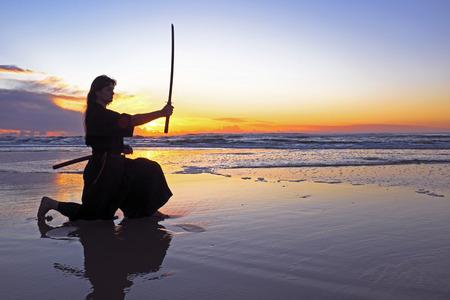 Jonge samurai vrouwen met een Japans zwaard Katana bij zonsondergang op het strand