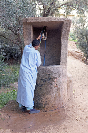 SAHARA DESERT, MOROCCO 20 OCTOBER 2013: Man in traditional clothes drinking water from the well