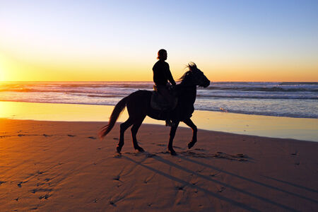 Horse riding on the beach at sunset Stock Photo