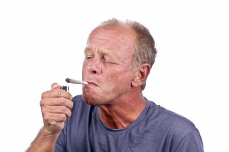doped: Man lightning a marihuana joint Stock Photo