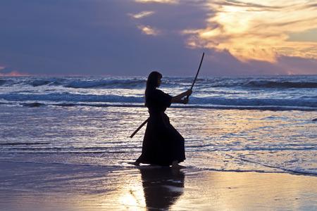 Jonge samurai vrouwen met een Japans zwaard (katana) bij zonsondergang op het strand