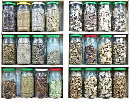 herbolaria: Surtido de tarros de cristal en los estantes en la tienda de herbolario en Marrakech, Marruecos, que contiene hierbas y especias con fines medicinales y culinarias