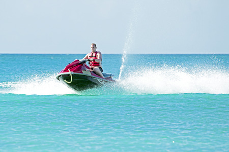 Young guy cruising on a jet ski on the caribbic sea