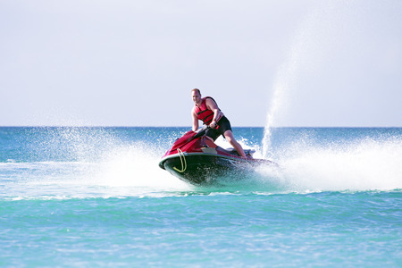 Young guy cruising on the atlantic ocean on a jet ski Stockfoto