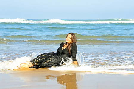 Beautiful woman in the water from the ocean photo